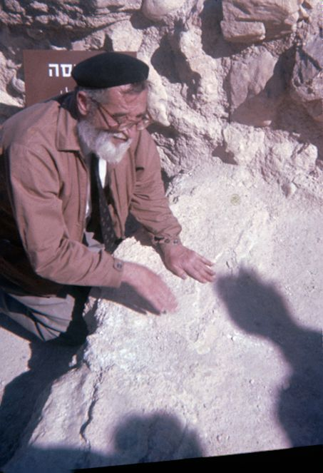 Qumran (1970-71). Fr. Roland de Vaux demonstrating how clothing was laundered at Qumran, where items were washed and patted dry on flat stone.  From the collection of Professor Philip Davies, Emeritus Professor at the University of Sheffield